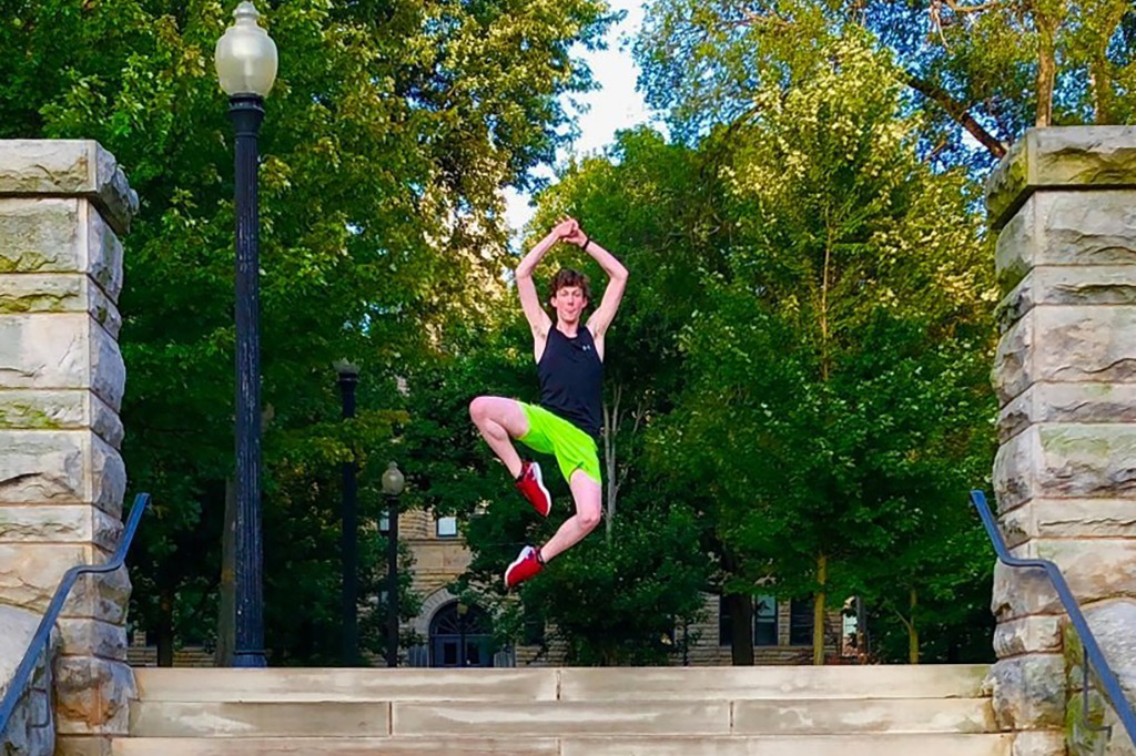Male dance student leaping above stone outdoor steps