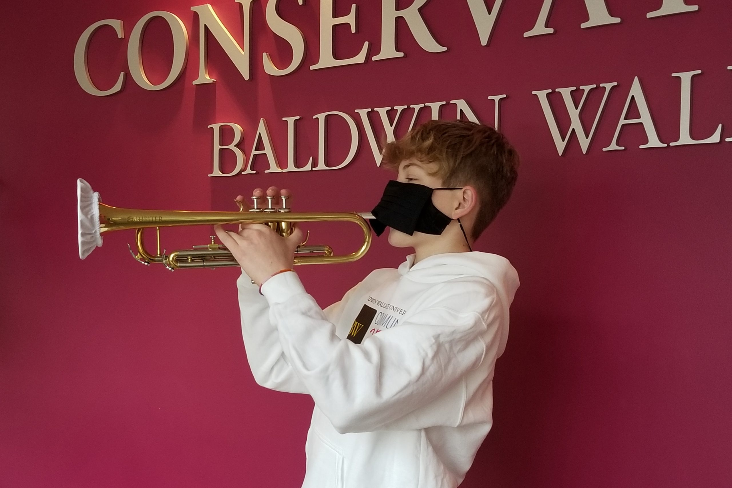 Middle school camp student playing trumpet with face covering and bell cover